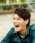 Young Asian man, bursting out laughing outside.
