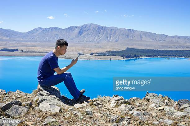 young asian man with mobile phone sitting by lake