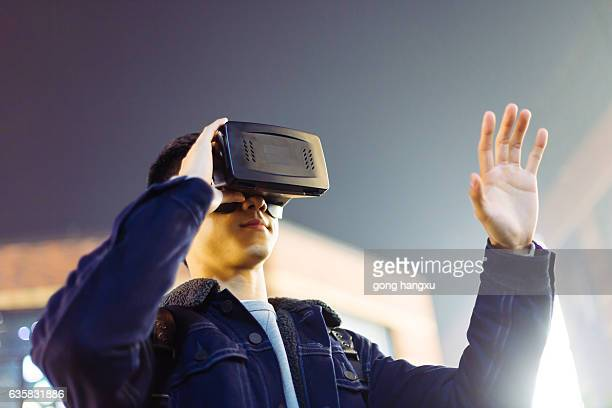 young asian man with VR on street at night