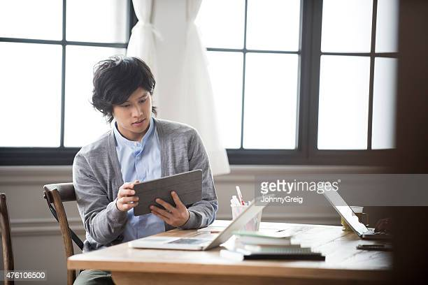 Young Asian man working with digital tablet