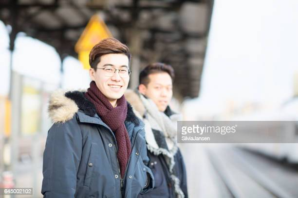 young asian men traveling with train