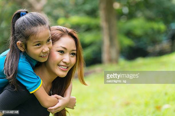 Young Asian Mother and School Age Daughter in City Park
