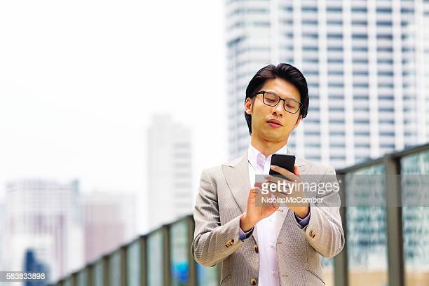 Young Asian office worker gaming on mobile phone