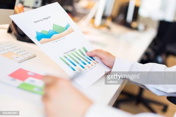 Junge asiatische Büroangestellter mit Diagrammen