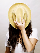 Young asian woman covering face with a straw hat