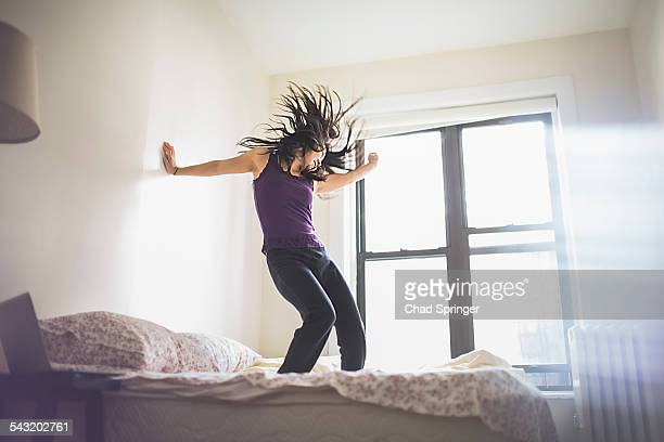 Young Asian woman dancing on bed