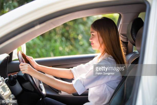 Young asian woman driver driving a car on the road in countryside.