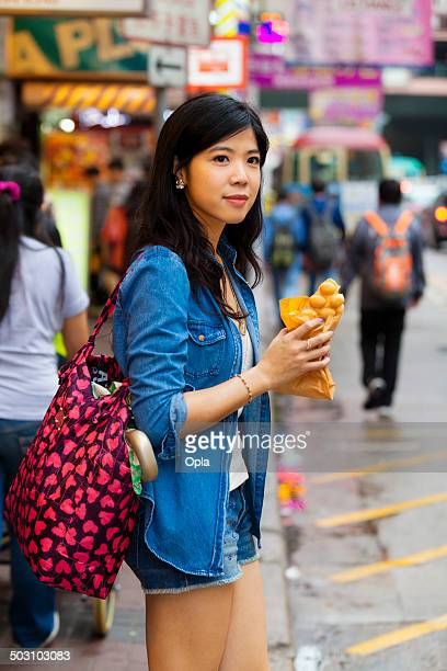 Young Asian woman eating Egg Waffle
