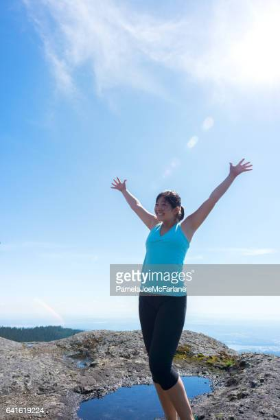 Young Asian Woman Embracing Nature with Open Arms on Mountaintop