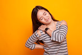 Young Asian woman got back pain on yellow background
