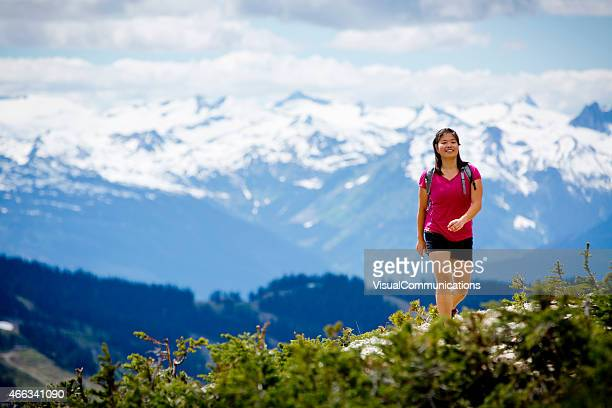 Young Asian woman hiking in mountains.