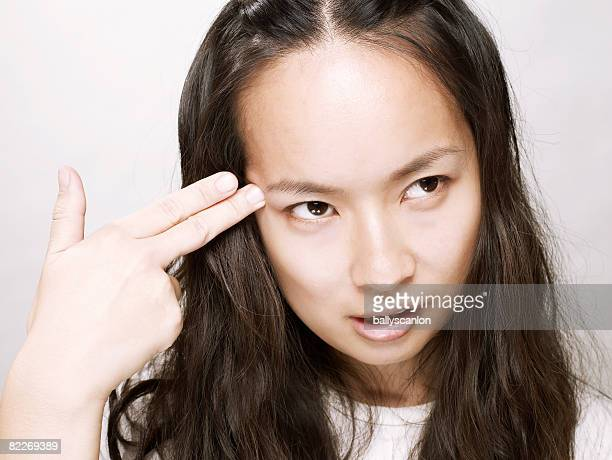 Young asian woman holding hand to her head