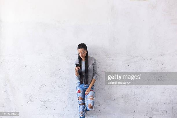 Young asian woman leaning back on blank wall