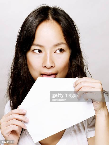 Young asian woman licking envelope