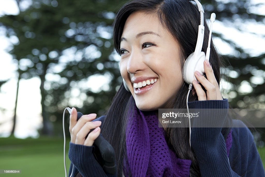 Young Asian woman listening to music : Stock Photo