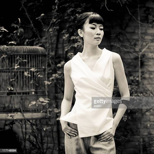 Young asian woman next to bird cage
