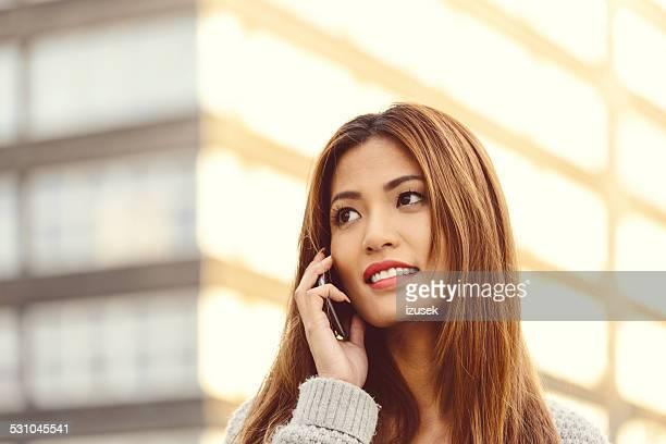 Young asian woman on phone outdoor