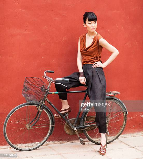 Young asian woman posing sitting on bicycle