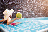 Young asian woman relaxing in swimming pool at spa resort.relaxing and spa relax concept.