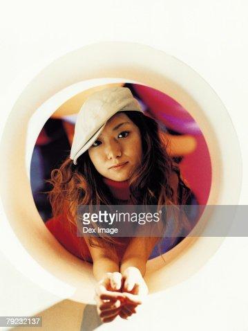 Young Asian woman, round shape window : Stock Photo
