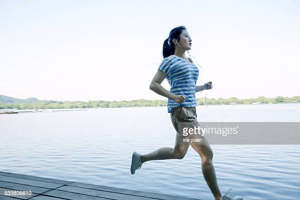 Young asian woman running on pier against lake