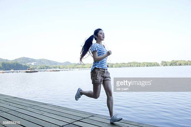 Young asian woman running on pier for exercise