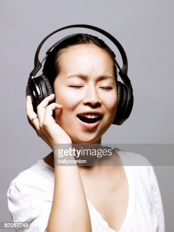 young asian woman singing wearing headphones stock photo