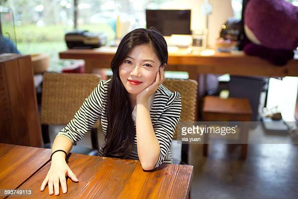 Young asian woman sitting by table,hand on chin