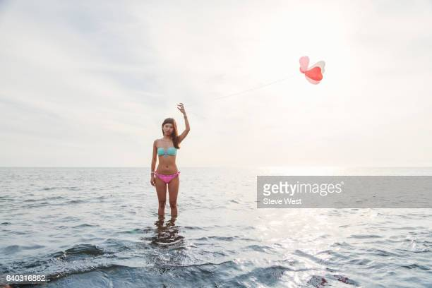 Young Asian Woman Standing In The Ocean Holding Balloons