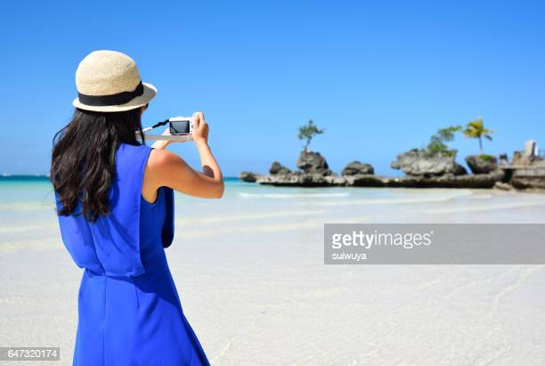 Young asian woman take picture using smartphone at beach