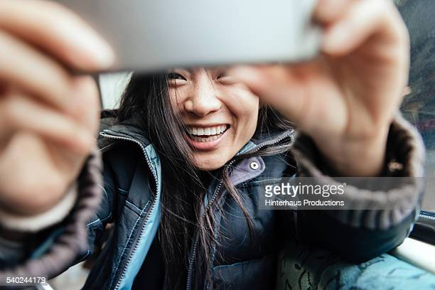 Young Asian Woman Taking Selfie In Train