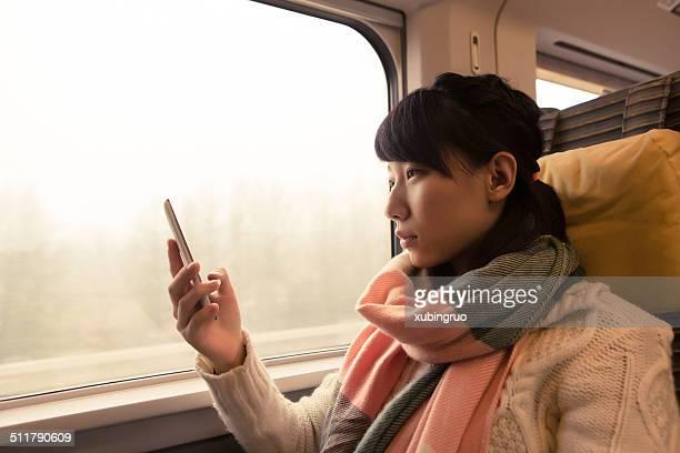若いアジア人の女性が列車でご旅行