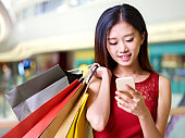 beautiful young asian woman carrying colorful paper bags on shoulder looking at mobile phone in modern shopping mall