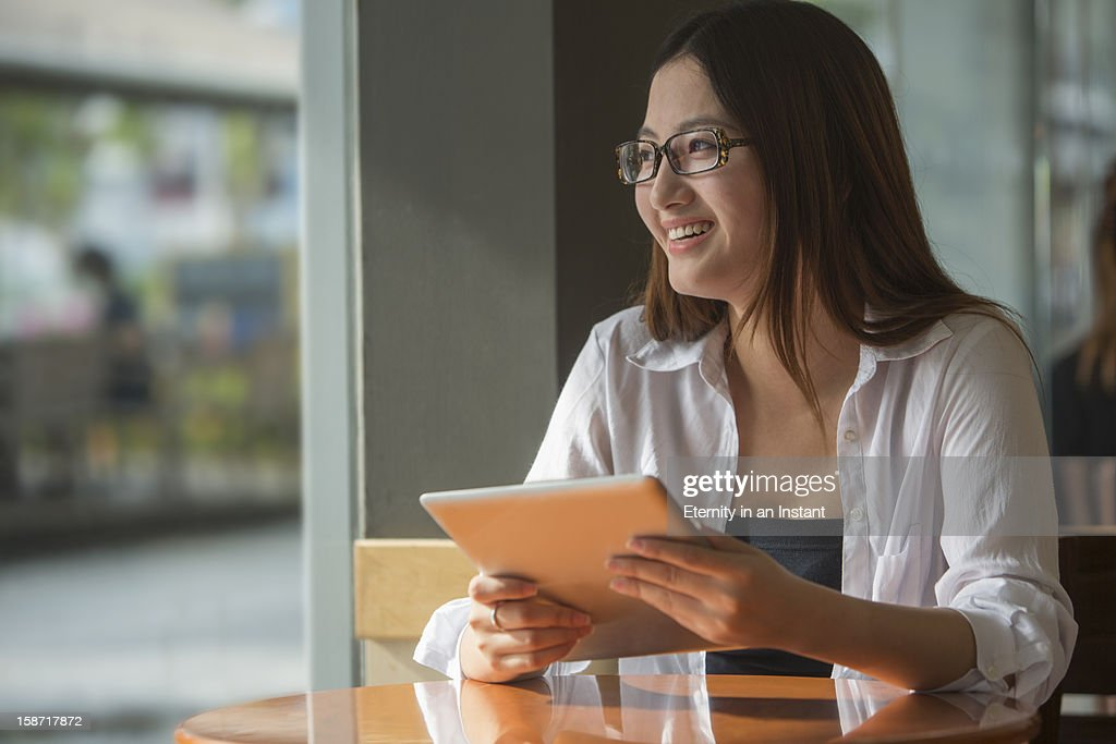 Young Asian woman using digital tablet in cafe : Stock Photo