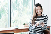 Young asian woman using smart phone while sitting by window cafe background, People technology and lifestyle