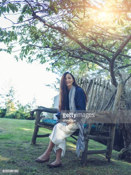 young asian woman using tablet,sitting on the garden bench at backyard
