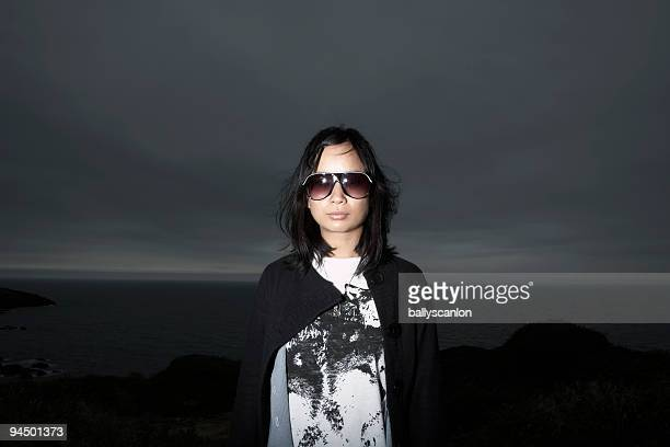 Young Asian Woman Wearing Sunglasses By The Sea.