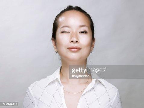 Young Asian woman, winking at camera. : Stockfoto