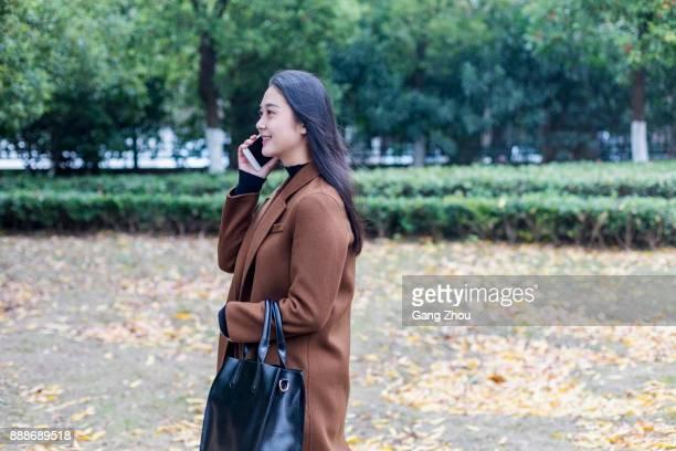 young asian woman with black handbag talking on street