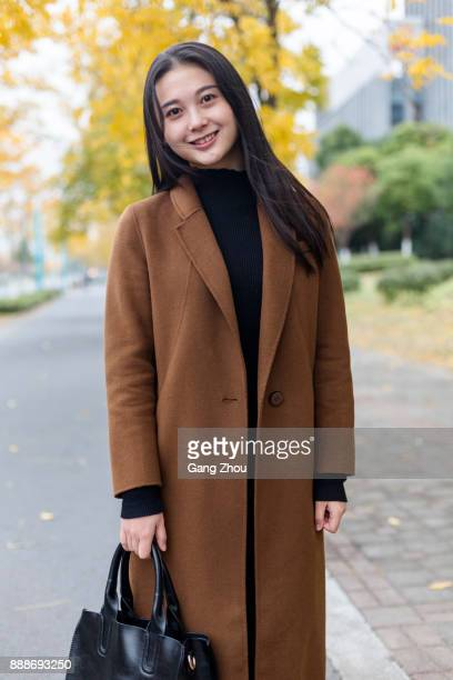 jonge Aziatische vrouw met zwarte handtas lopen op straat
