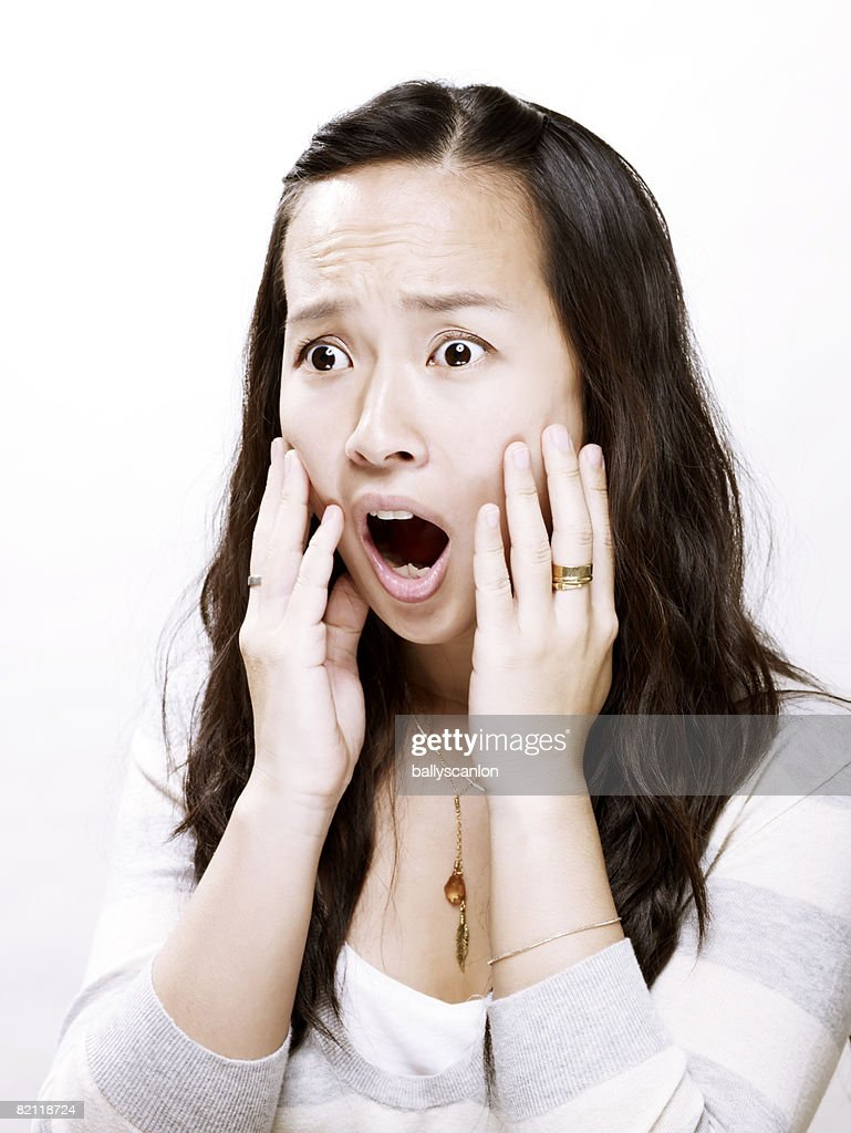 young asian woman with hands to her face in shock : Stock Photo