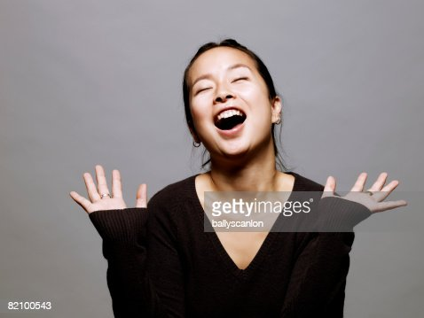 young asian woman with hands up, laughing : Stock Photo