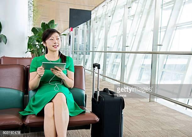 Junge asiatische Frau mit tablet in departure area