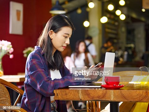 young asian woman working in coffee shop using and cellphone laptop computer : Stock Photo
