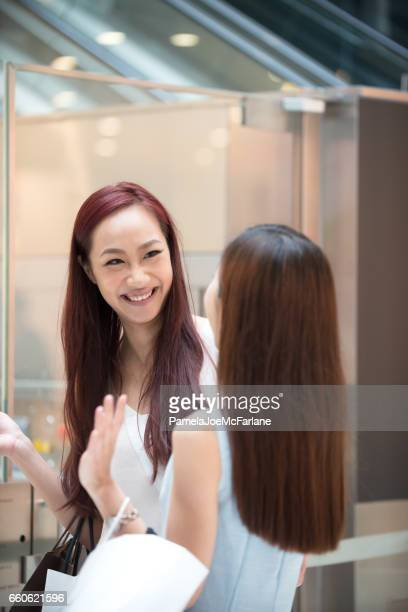 Young Asian Women Friends Laughing and Shopping in Mall