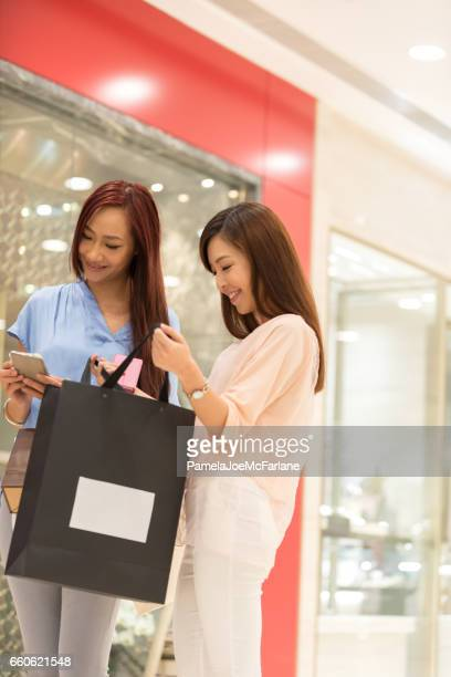 Young, Asian Women Shopping in Mall, Texting and Admiring Purchases
