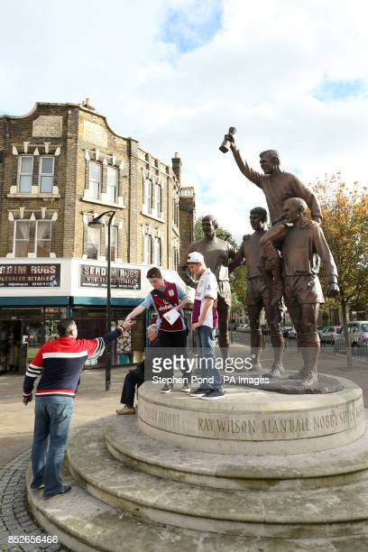 Young Aston Villa fans stand on the monument to the English World Cup winning West Ham players Ray Wilson Alan Ball Nobby Stiles and Bobby Moore