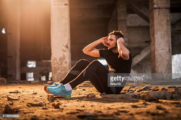 Young athlete doing sit-ups in a ruin.