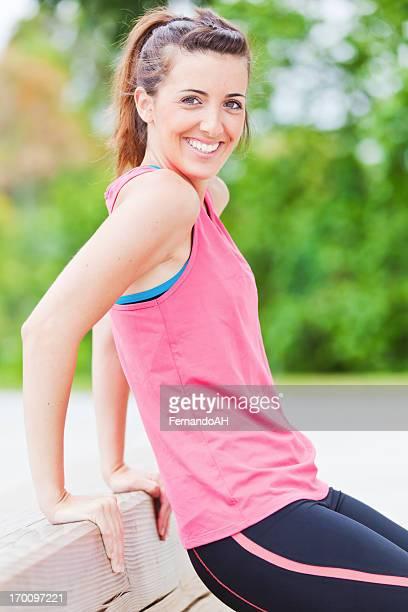 Junge Sportler tun Trizeps Übungen mit einer Bank