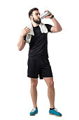 Young athlete drinking smoothie from plastic container with towel around neck. Full body length isolated over white studio background.